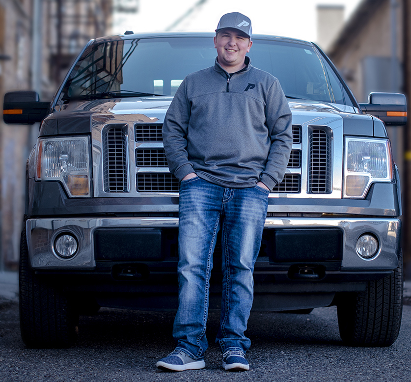 Tech Sales Rep Cody Lords stands with his 2012 Ford F-150 EcoBoost